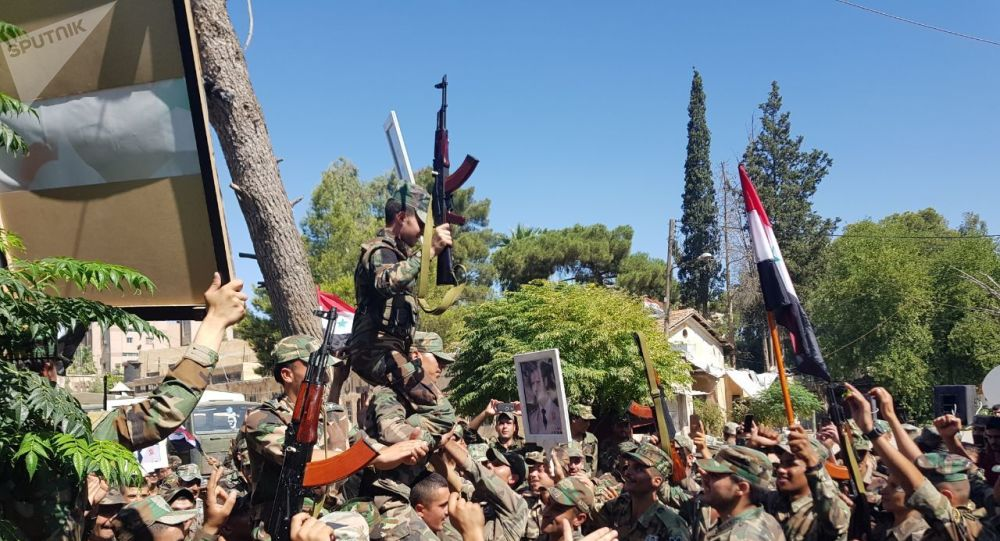 جنود سوريون يحتفلون بعيد الجيش وسط غابة من القواعد الأمريكية