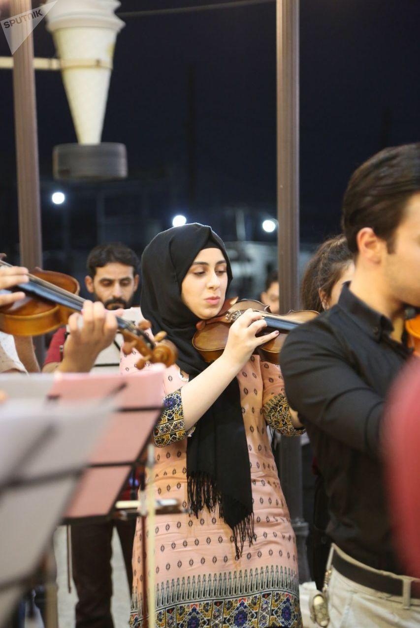 موسيقيات وعازفون في أوركسترا مضيئة في العراق