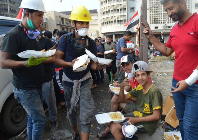 أطفال يتناولون أطباقا من وجبة برياني دجاج، توزع مجانا على المتظاهرين، في التحرير، بغداد