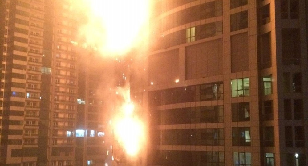 This photo provided by Rhea Saran shows flames coming from a high rise tower in Dubai's marina district Saturday, Feb. 21, 2015.