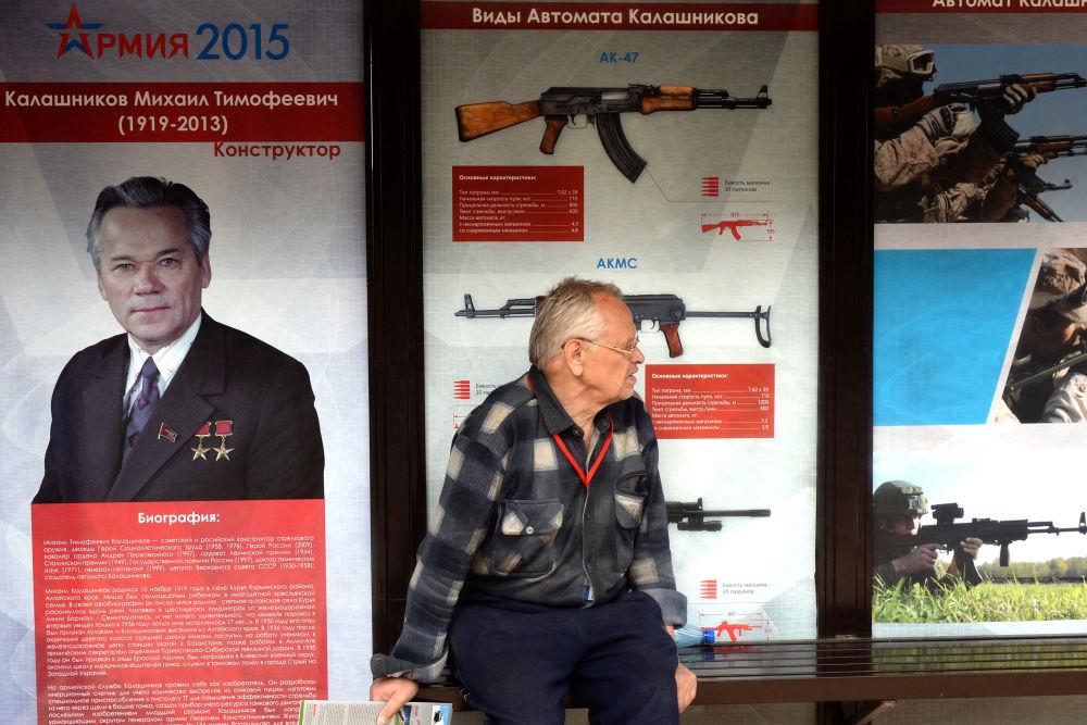 رجل ينتظر الحافلة وخلفه دعاية كلاشينكوف في مدينة كوبينكا