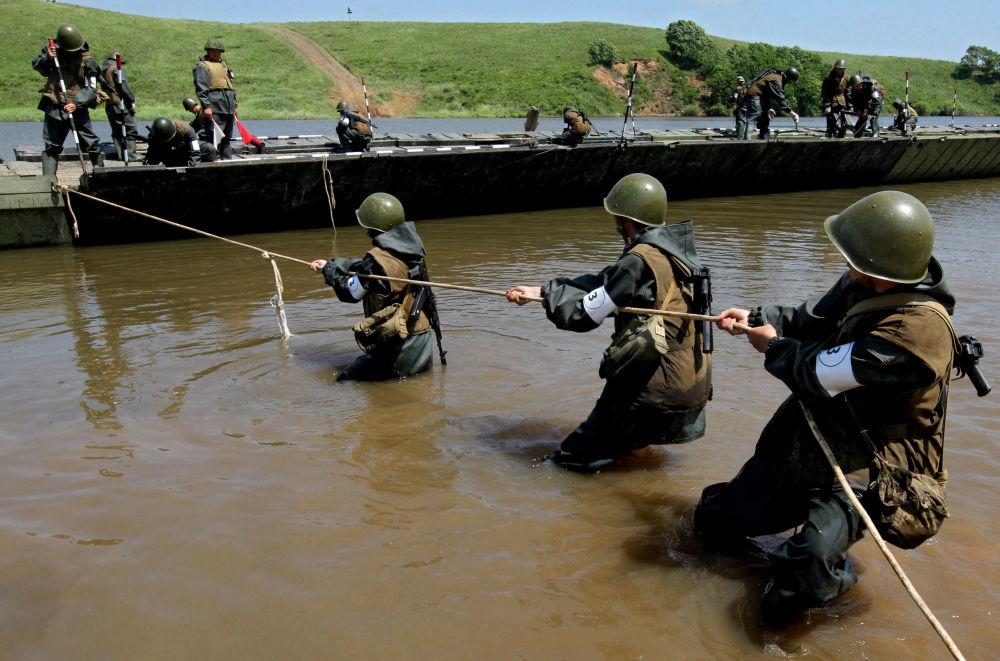 جنود القوات الهندسية خلال التدريبات يشيدون جسر عائم