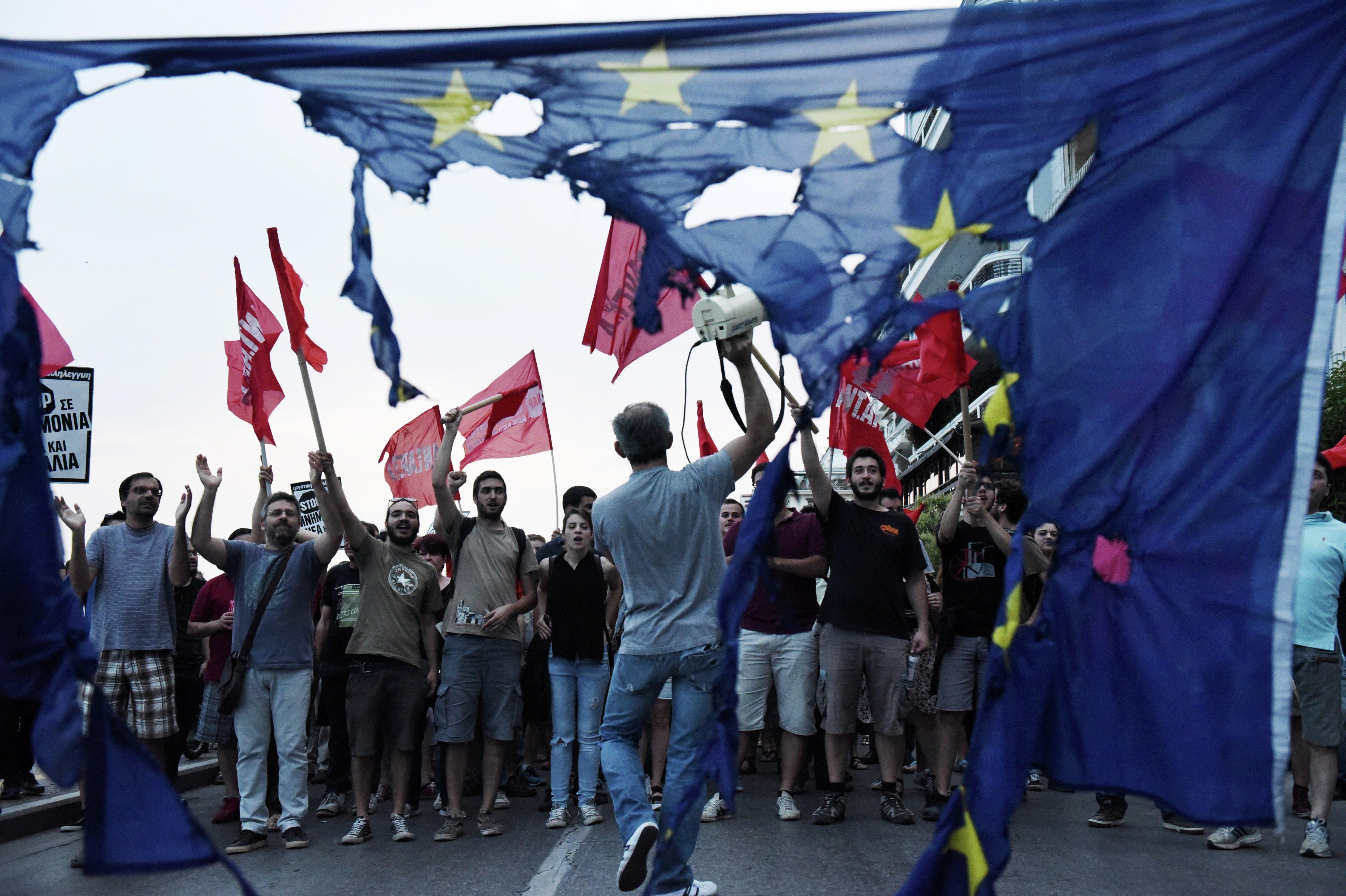 متظاهرون يونانيون يمزقون علم الإتحاد الأوروبي خلال مسيرة إحتجاجية