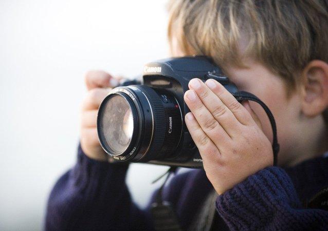 طفل يمسك كاميرا