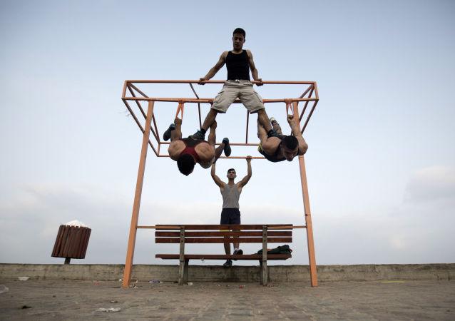 عدد من الشباب الفلسطيني يمارس تمارين رياضية في أحد الشوارع على ساحل البحر في غزة