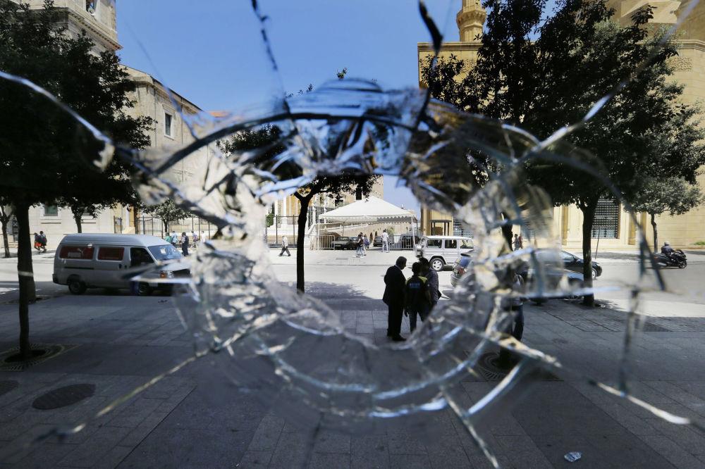 ثقب في واجهة محل تجاري، من آثار اشتباكات ليلية بين المتظاهرين والشرطة في لبنان