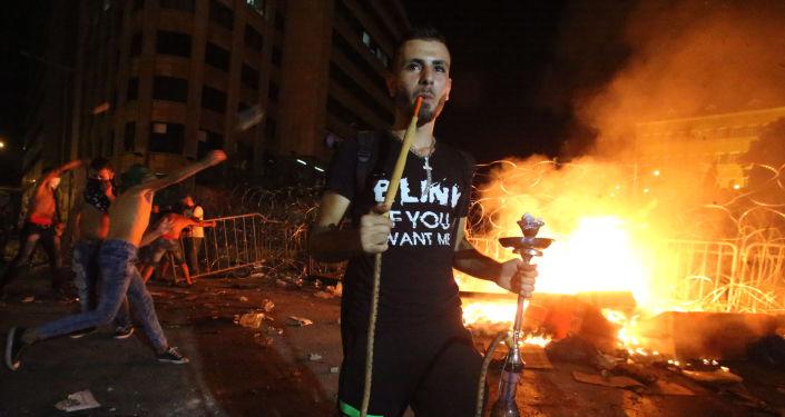 متظاهر لبناني يدخن الأركيلة (الشيشة) أثناء اشتباكات مع قوات الأمن