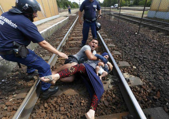 عناصر من الشرطة الهنغارية يحاولون منع أسرة من المهاجرين من العبور عبر محطة للسكك الحديدية المجر، 3 سبتمبر 2015.