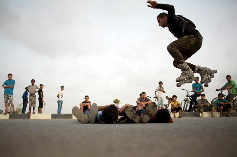 متزلج فلسطيني يقفز فوق الصبية الصغار نيام على الأرض ، وذلك خلال لقائهم الأسبوعي لممارسة رياضتهم في حي الزهراء، في ضواحي مدينة غزة.
