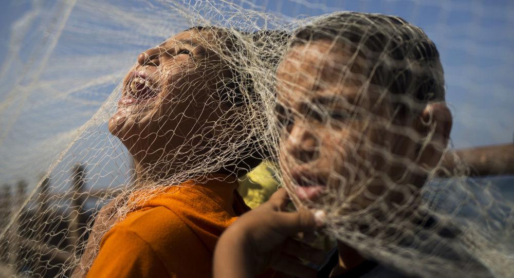 أطفال قطاع غزة يلعبون بشباك صيد السمك