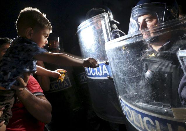 طفل يمد يده إلى درع الشرطي في كرواتيا