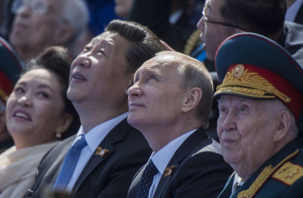 الرئيس الروسي فلاديمير بوتين والرئيس الصيني شي جين بينغ بصحبة عقيلته أثناء العرض العسكري بمناسبة الذكرى الـ70 لعيد النصر في الحرب العالمية الثانية