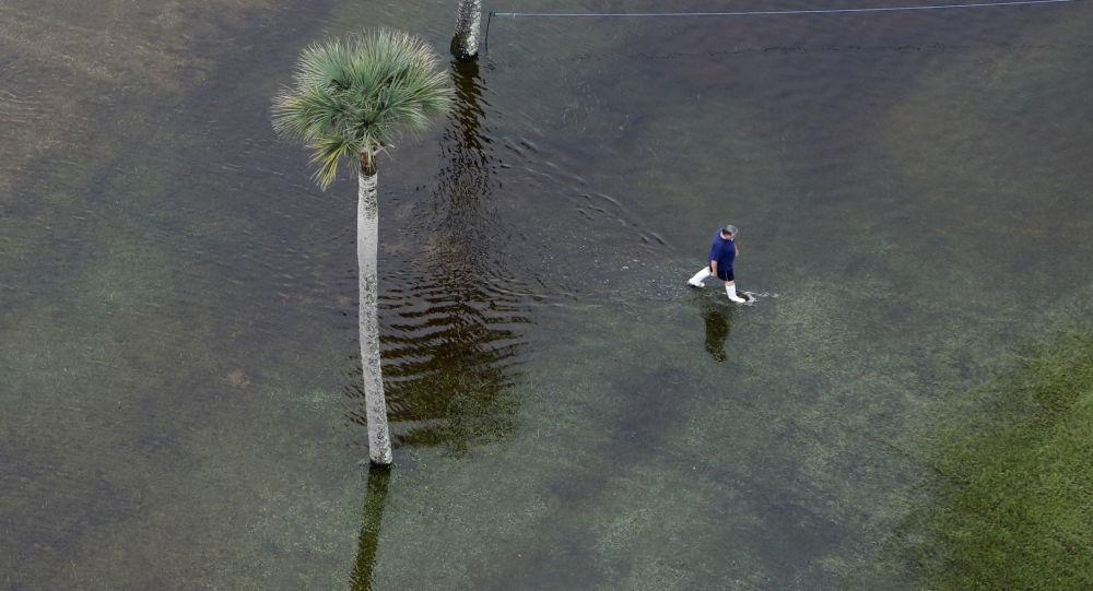 رجل يمشي في مياه غفيرة نتجت عن فيضانات كبيرة ف جزريرة النخيل في كارولينا الجنوبية، بالولايات المتحدة الأمريكية.
