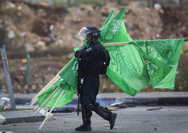 ضابط اسرائيلي يجمع اعلام حماس