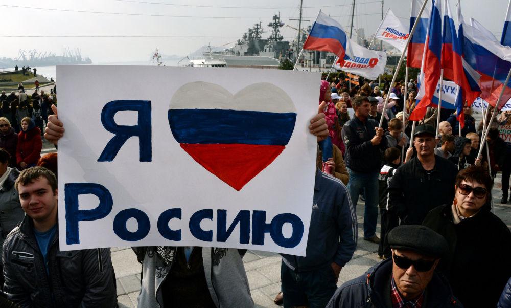 مواطن من فلاديفوستوك الروسية يحمل لوحة كُتب عليها أنا أحب روسيا، وذلك خلال فعالية الاحتفال بيوم وحدة الشعوب.