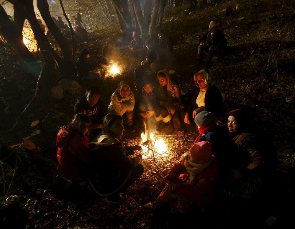 المهاجرون يتدفون حول نار في منطفة لا تبعد كثيراً عن الحدود المجرية.