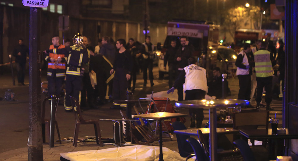 Rescue workers and medics work by victims in a Paris restaurant, Friday, Nov. 13, 2015. Police officials in France on Friday reported a shootout in a Paris restaurant and an explosion in a bar near a Paris stadium.