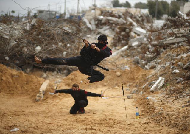 شاب فلسطيني يقفز حاملاً سيفه، مقدماً بذلك مهارات النينجا، من أمام المباني المدمرة إثر الحرب الأخيرة 2014، شمال قطاع غزة، 29 يناير/ كانون الثاني 2016.