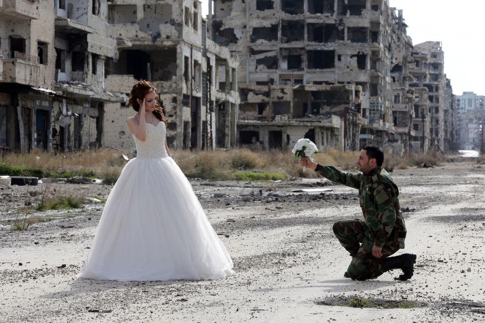 ندى مرحي (18 عاماً) وحسن يوسف (27 عاماً)، عروسان جديدان يلتقطان صور زفافهما وسط دمار المباني والمنازل في مدينة حمص المهجورة، 5 فبراير/ شباط 2016.
