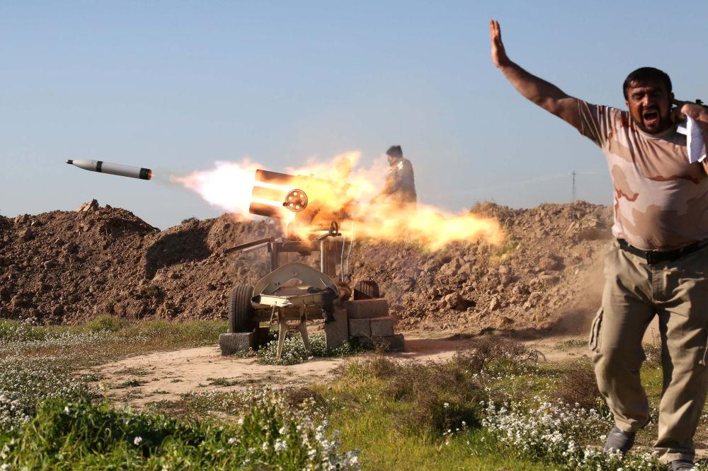 محارب عراقي يغلق آذانه عند إطلاق الصواريخ في شمال غرب العراق، 16 فبراير/ شباط 2016.