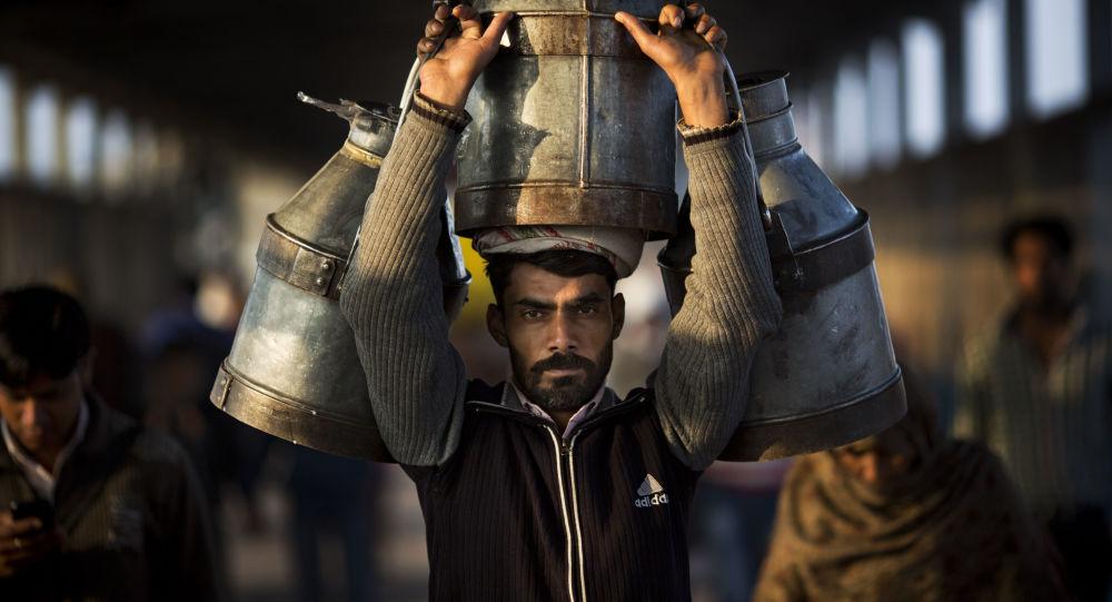 رجل هندي يحمل جراتحليب على محطة قطارغازي آباد في الهند، 24 فبراير/ شباط 2016.