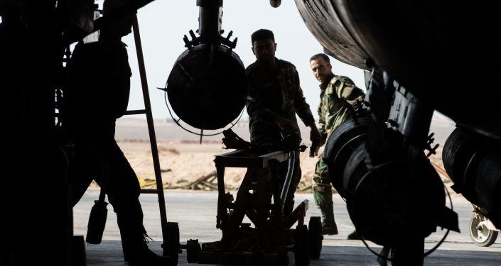 عناصر الجيش السوري يجهزون المقاتلة سو-22 للإقلاع من القاعدة الجوية السورية في محافظة حمص.