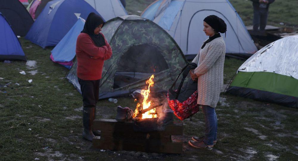 فتيات لاجئات يتدفون على نار الحطب في إحدى المخيمات على الحدود الينونانية-المقدونية، 1 مارس/ آذار 2016.