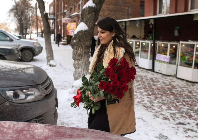 امرأة تحمل باقة من الورد فى مدينة أومسك الروسية