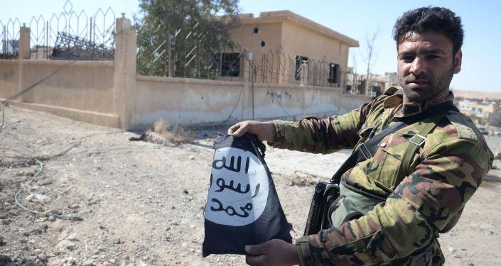 جندي من الجيش العربي السوري يحمل علم تنظيم داعش في مدينة القريتين، وذلك بعد تحريرها من التنظيم.