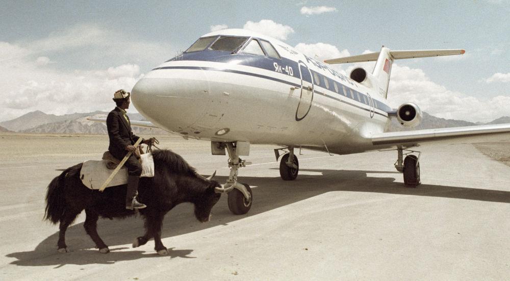 مواطن طاجيكي يسير بالقرب من طائرة ياك-40.