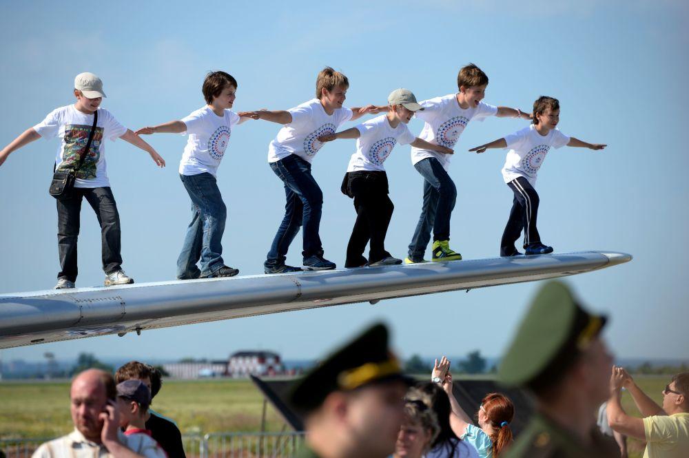 أطفال يلتقطون صورة جماعية على جناح طائرة ياك-40 في مطار سوكول في البيرم، روسيا.