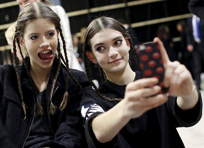 عارضات أزياء يلتقطون صورة سيلفي خلف كواليس عرض أسبوع الموضة في ميلانو، إيطاليا 27 فبراير/ شباط 2016.