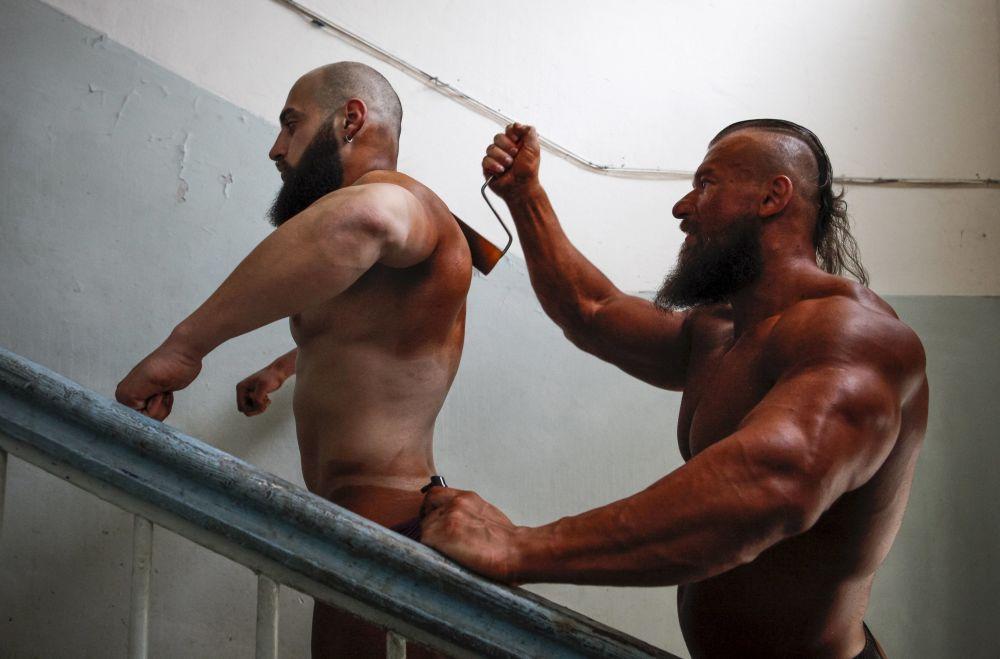 بطولة كمال الأجسام في ستارفبول بروسيا - متسابق يدهن جسم متسابق آخر