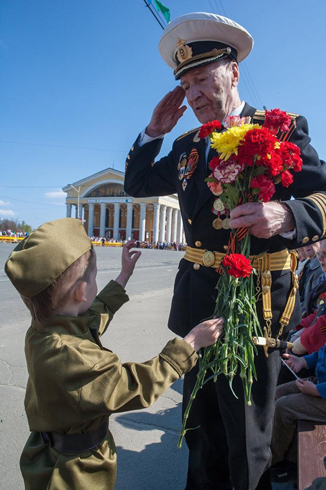 طفل يحي ويهنئ محارب قديم شارك في الحرب الوطنية العظمى (1941-1945)