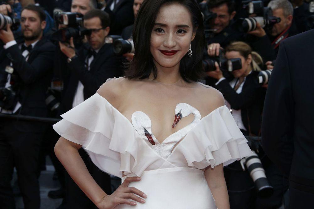 ضيفة تستعرض فستانها على  السجادة الحمراء خلال الفعالية الـ 69 لافتتاح مهرجان كان الفرنسي
