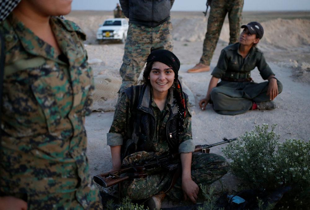 فتيات في قوات حزب العمال الكردي تبتسم للكاميرا وهي تحمل بندقية قنص، شمال العراق 29 أبريل/ نيسان 2016.