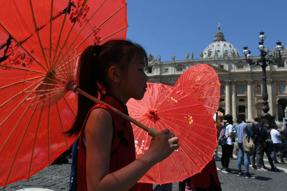 طفلة تحمل مظلة حمراء وتسير من أمام مقر بابا الفاتيكان في الفاتيكان، 22 مايو/ آيار 2016.