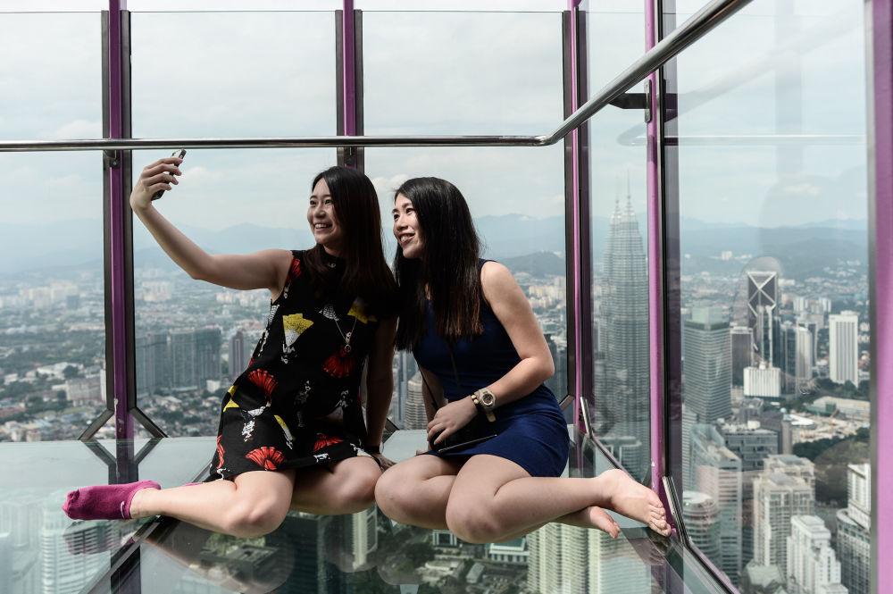 فتاتان ماليزيتان تلتقطتان صورة سيلفي لهما على خلفية مدينة كوالا لامبور، 24 مايو/ آيار 2016.