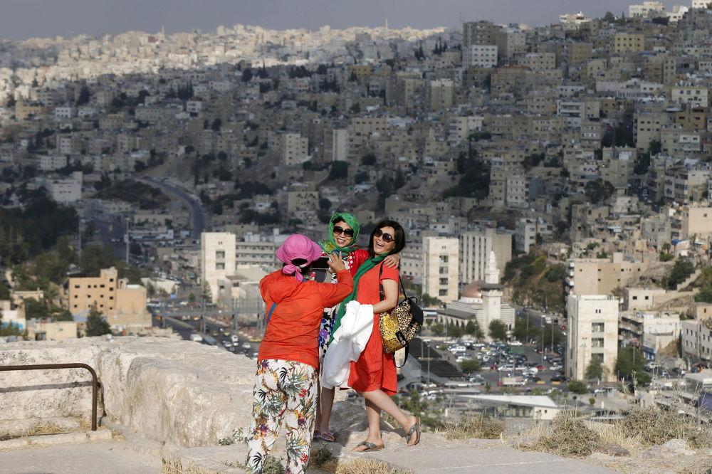 السياح الصينيون يأخذون صوراً على خلفية العاصمة الأردنية عمان، 23 مايو/ آيار 2016.