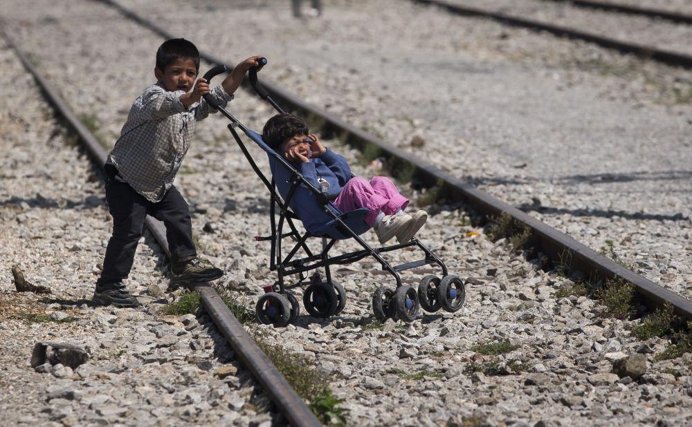 طفلين لاجئين، أحدهما يدفع بالآخر في قرية إيدوميني باليونان، 22 مايو/ آيار 2016.