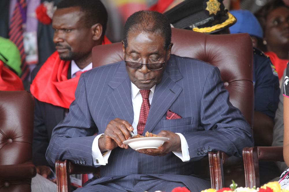 رئيس زيمبابوي روبيرت موغابي يأكل قطعة الكيك خلال الاحتفال بعيد ميلاده الـ 92، عام 2016