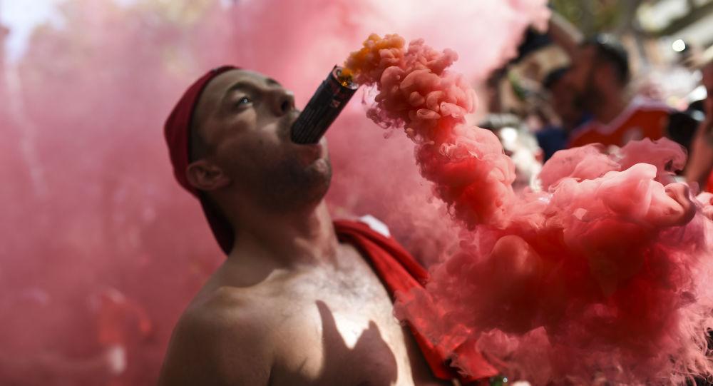 مشجع منتخب ويلز وهو يمسك بفمه شمروخ