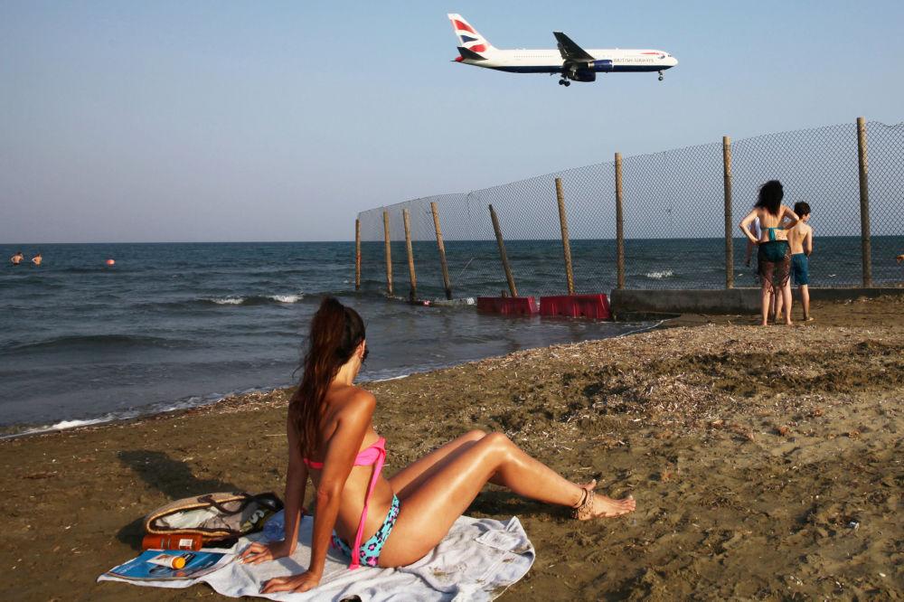بعض الأشخاص يستجمون ويشاهدون طائرة الخطوط الجوية البريطانية