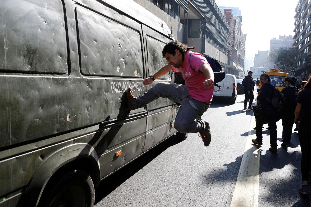 متظاهر يضرب شاحنا تابعا للشرطة التشيلية خلال الاحتجاجات، التي نظمها اتحاد الطلاب، احتجاجا على تعديلات أجرتها الحكومة على التعليم الحكومي في سانتياغو، 5 يوليو\ تموز 2016