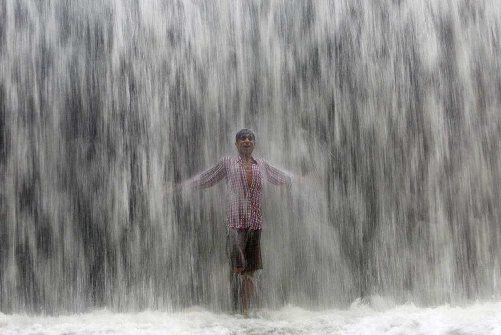صبي يقف تحت شلال المياه في مومباي بالهند، 4 يوليو\ تموز 2016