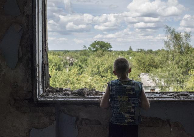 مراهق على شرفة مدرسة دمرت نتيجة قصف بقرية شاختي في جمهورية دونيتسك، أوكرانيا