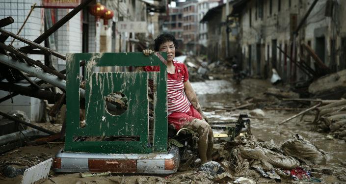 امرأة تجلس وسط شارع في الصين بعد طوفان ضرب البلاد، 10 يوليو/ تموز 2016.