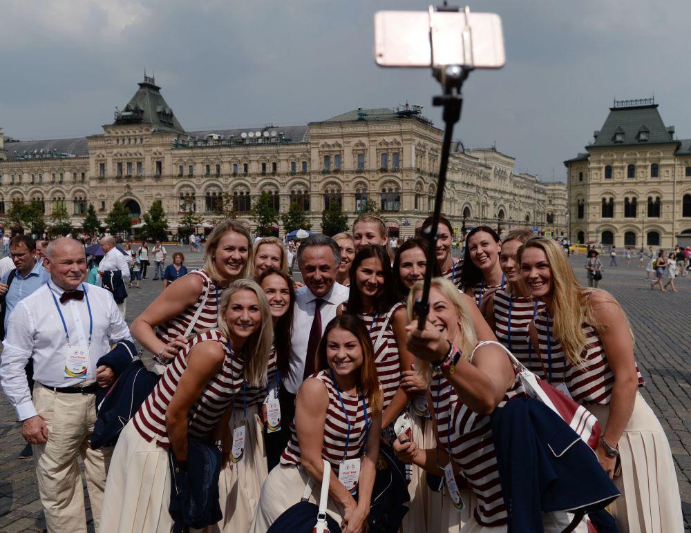 الفريق الرياضي الأولمبي الروسي يلتقط صورة جماعية مع وزير الرياضة الروسي  فيتالي موتكو على خلفية الساحة الحمراء في موسكو.