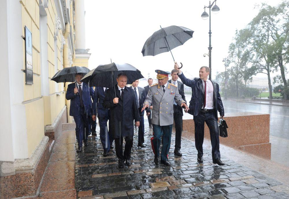 الرئيس فلاديمير بوتين و وزمير الدفاع الروسي سيرغي شويغو، يسيران تحت أمطار غزيرة، ويشاركون في احتفالات عيد قوات الإنزال الجوي الروسية، سانت بطرسبورغ.