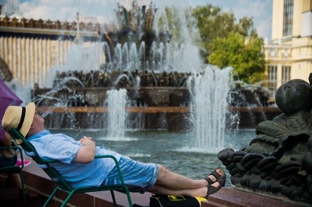 المواطنون الروس يجلسون بالقرب من نافورة المياه كايني تسفيتوك (الزهرة الحجر) في حديقة مركز معارض عموم روسيا في موسكو